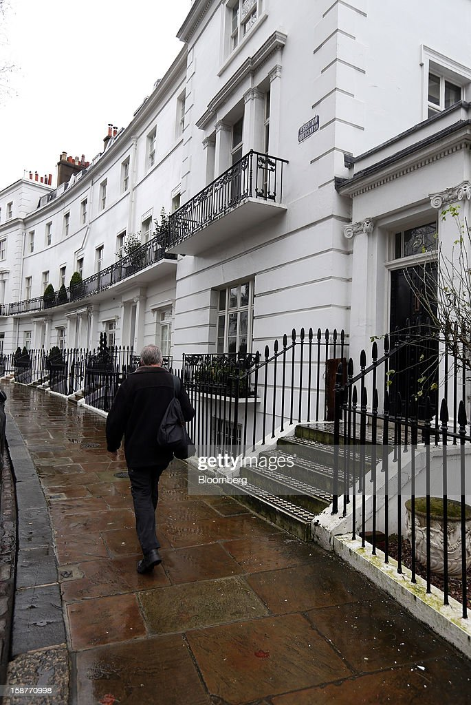 A pedestrian passes a row of houses on Egerton Crescent in the Kensington and Chelsea borough of London, U.K., on Friday, Dec. 28, 2012. Egerton Crescent, close to Harrods luxury department store in Knightsbridge, is the most expensive address in the borough, with an average property value of 8.14 million pounds ($13.2 million), Lloyds TSB said. Photographer: Chris Ratcliffe/Bloomberg via Getty Images