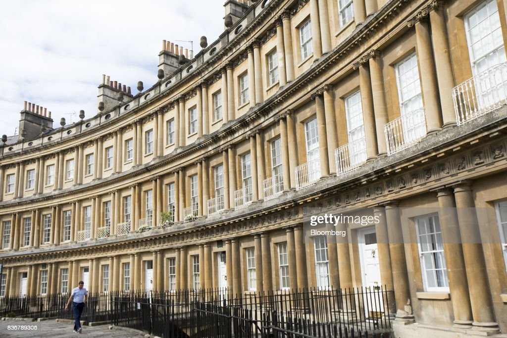 A pedestrian passes a row of terraced houses on a suburban street in Bath, U.K. on Monday, Aug. 21, 2017. U.K. property prices stagnated in July as a slump in London values spread to neighboring areas, according to theRoyal Institution of Chartered Surveyors. Photographer: Jason Alden/Bloomberg via Getty Images