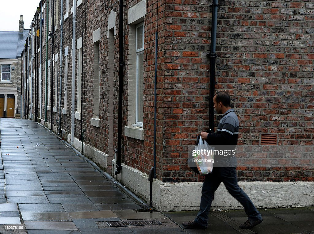 A pedestrian passes a row of terraced residential houses in Newcastle-upon-Tyne, U.K., on Wednesday, Sept. 11, 2013. U.K. house prices rose for a seventh month in August and will probably continue to increase through the rest of the year, according to a report by Halifax. Photographer: Nigel Roddis/Bloomberg via Getty Images