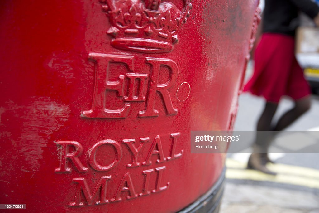 A pedestrian passes a Royal Mail Group Ltd. pillar box in London, U.K., on Friday, Sept. 13, 2013. Royal Mail Group Ltd., the U.K.'s 360-year-old postal service, intends to hold an initial public offering of a majority stake 'in the coming weeks' to help the company gain a competitive edge against European rivals. Photographer: Simon Dawson/Bloomberg via Getty Images