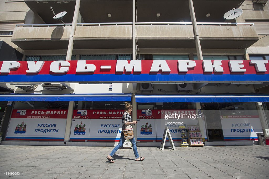 A pedestrian passes a Russian supermarket, branded in the colors of the Russian Federation, in Limassol, Cyprus, on Tuesday, April 8, 2014. Cyprus wants to shield financial flows with Russia, where it's the biggest foreign investor, as the U.S. and the European Union ratchet up sanctions in response to President Vladimir Putin's annexing Crimea from Ukraine. Photographer: Andrew Caballero-Reynolds/Bloomberg via Getty Images