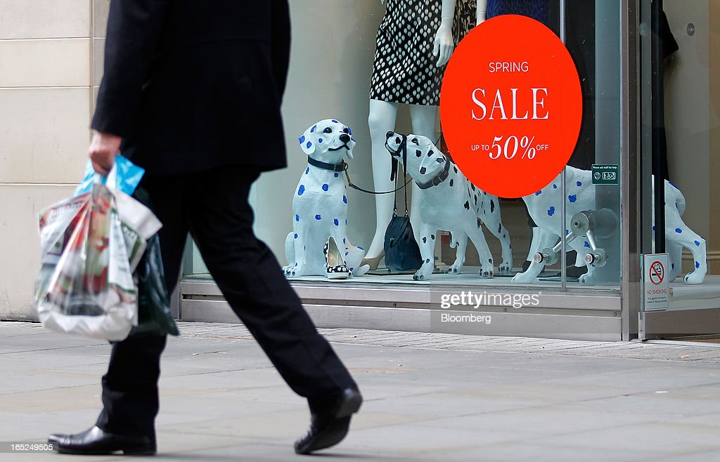 A pedestrian passes a sale sign in the window of a Hobbs store in Manchester, U.K., on Monday, April 1, 2013. U.K. retail sales unexpectedly stagnated in March in a sign that consumer spending remains under pressure from higher energy bills and weak wage growth. Photographer: Paul Thomas/Bloomberg via Getty Images