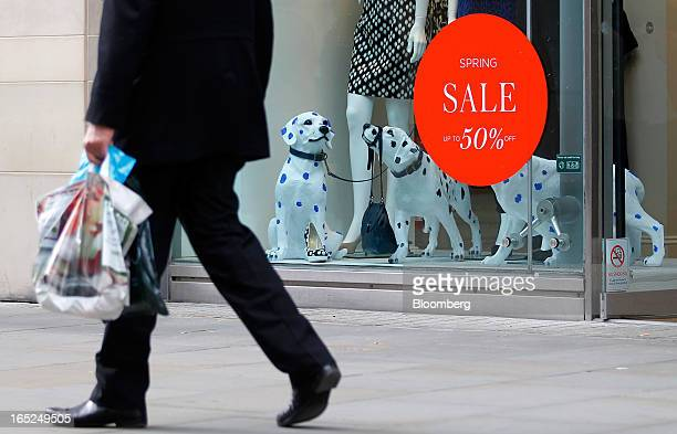 A pedestrian passes a sale sign in the window of a Hobbs store in Manchester UK on Monday April 1 2013 UK retail sales unexpectedly stagnated in...