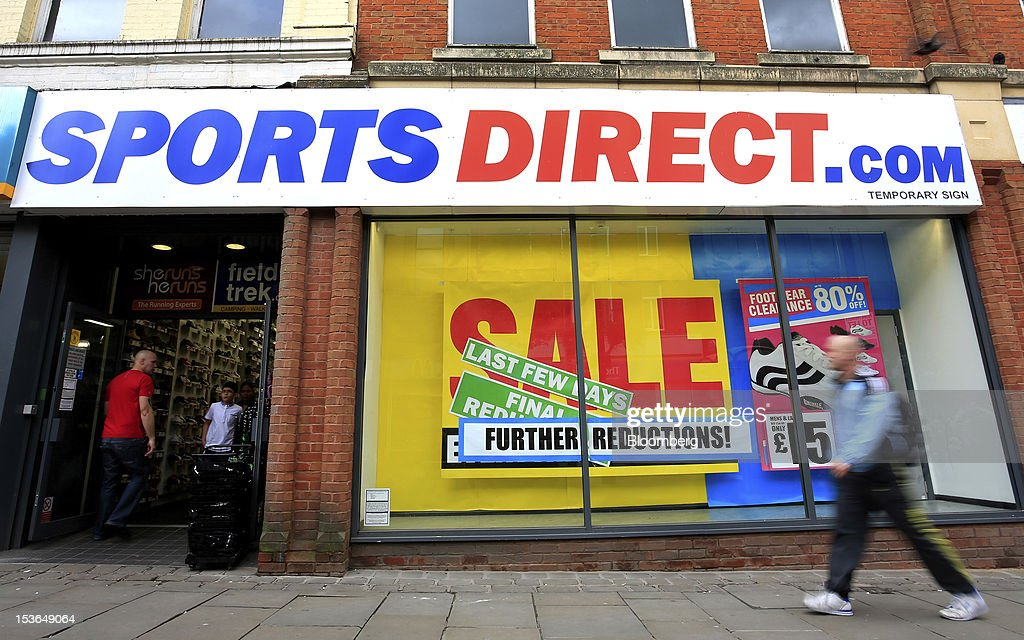 A pedestrian passes a sale sign in the window of a Sports Direct International Plc store in Oldham, U.K., on Saturday, Oct. 6, 2012. JJB Sports Plc, a U.K. sporting goods retailer, will close most of its stores with the remaining 20 being acquired by competitor Sports Direct International Plc, according to a statement from KPMG LLP, which was appointed as administrator to the Wigan, England-based company. Photographer: Paul Thomas/Bloomberg via Getty Images