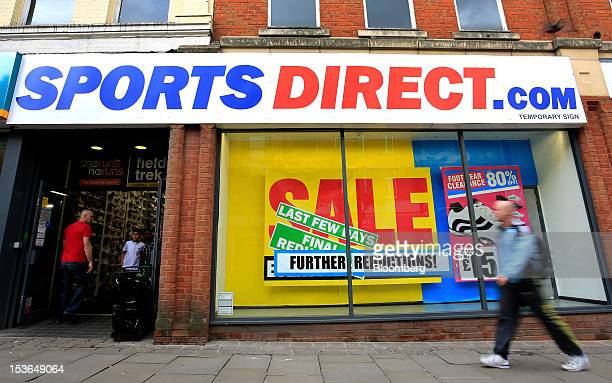 A pedestrian passes a sale sign in the window of a Sports Direct International Plc store in Oldham UK on Saturday Oct 6 2012 JJB Sports Plc a UK...