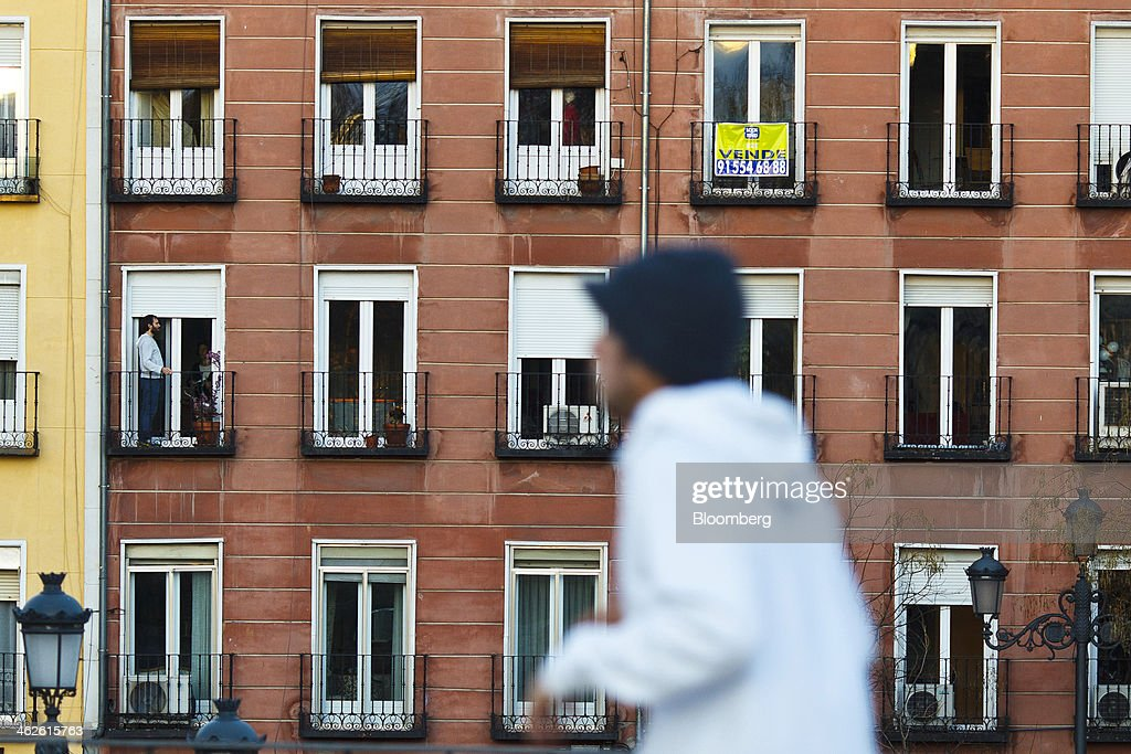 A pedestrian passes a sale sign on the balcony of a residential apartment in Madrid, Spain, on Monday, Jan. 13, 2014. Spain's rental market is growing as government-spending cuts, a 26 percent jobless rate and subdued mortgage lending make home buying more difficult. Photographer: Angel Navarrete/Bloomberg via Getty Images
