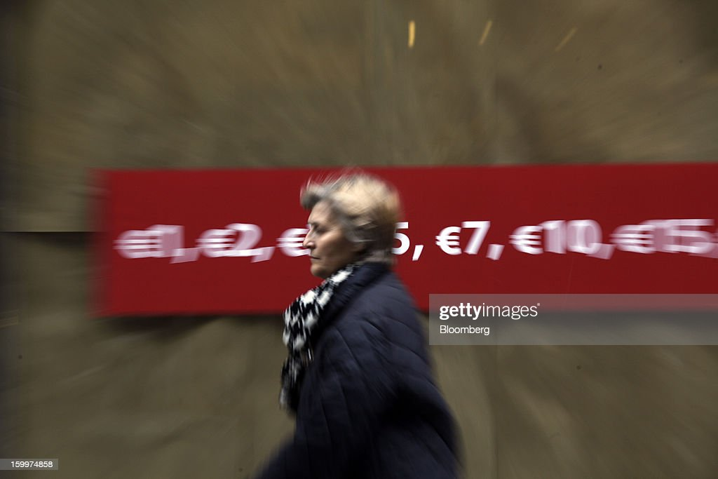 A pedestrian passes a sales discount advertisement in the window of a retail store in Athens, Greece, on Thursday, Jan. 24, 2013. Greece's government has implemented budget cuts and economic reforms to tame a fiscal deficit that has led to bailouts from the European Union and the International Monetary Fund. Photographer: Kostas Tsironis/Bloomberg via Getty Images