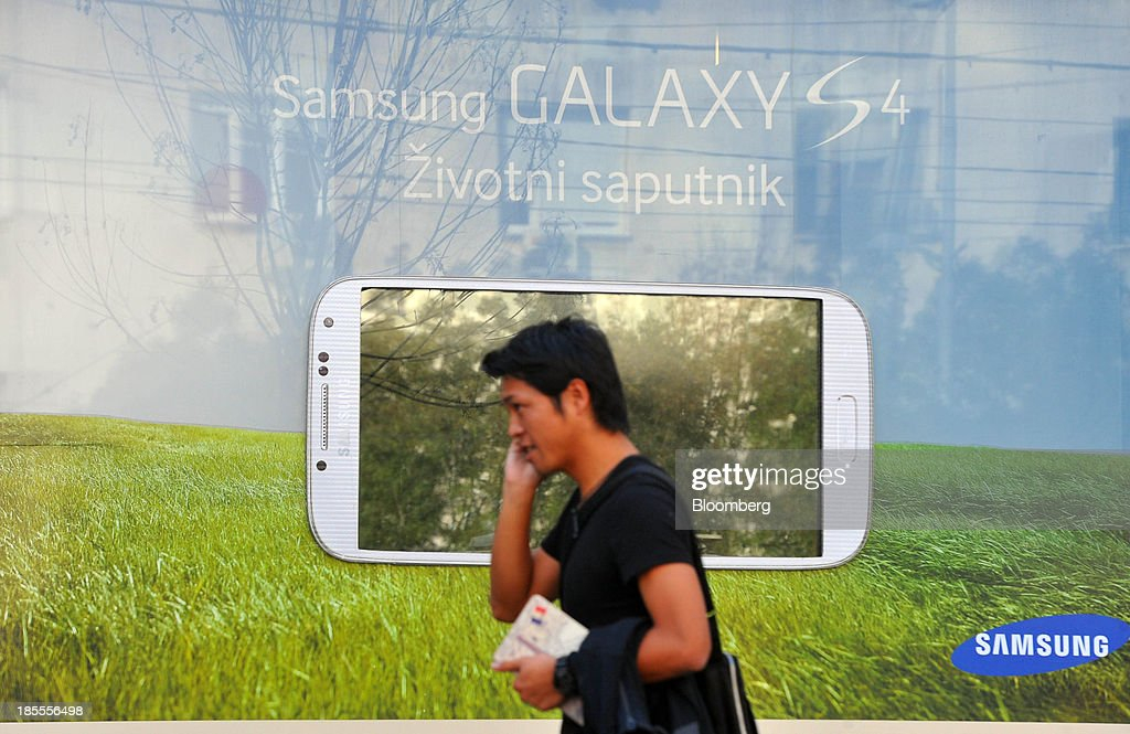 A pedestrian passes a Samsung Electronics Co. Ltd. advertisement for the Galaxy S4 smartphone in Belgrade, Serbia, on Monday, Oct. 21, 2013. Serbia's government revealed a salvo of measures to bring the public finance deficit and debt back under control by 2017 after the head of the largest coalition party warned the country was on the brink of insolvency. Photographer: Oliver Bunic/Bloomberg via Getty Images