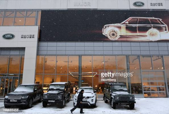 A pedestrian passes a selection of test drive automobiles outside a Jaguar Land Rover auto dealership in Moscow Russia on Thursday Dec 27 2012 Tata...