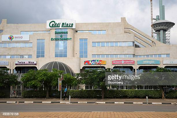 A pedestrian passes a shopping centre in Abuja Nigeria on Wednesday Oct 21 2015 A drop in crude prices in the past year has put pressure on public...