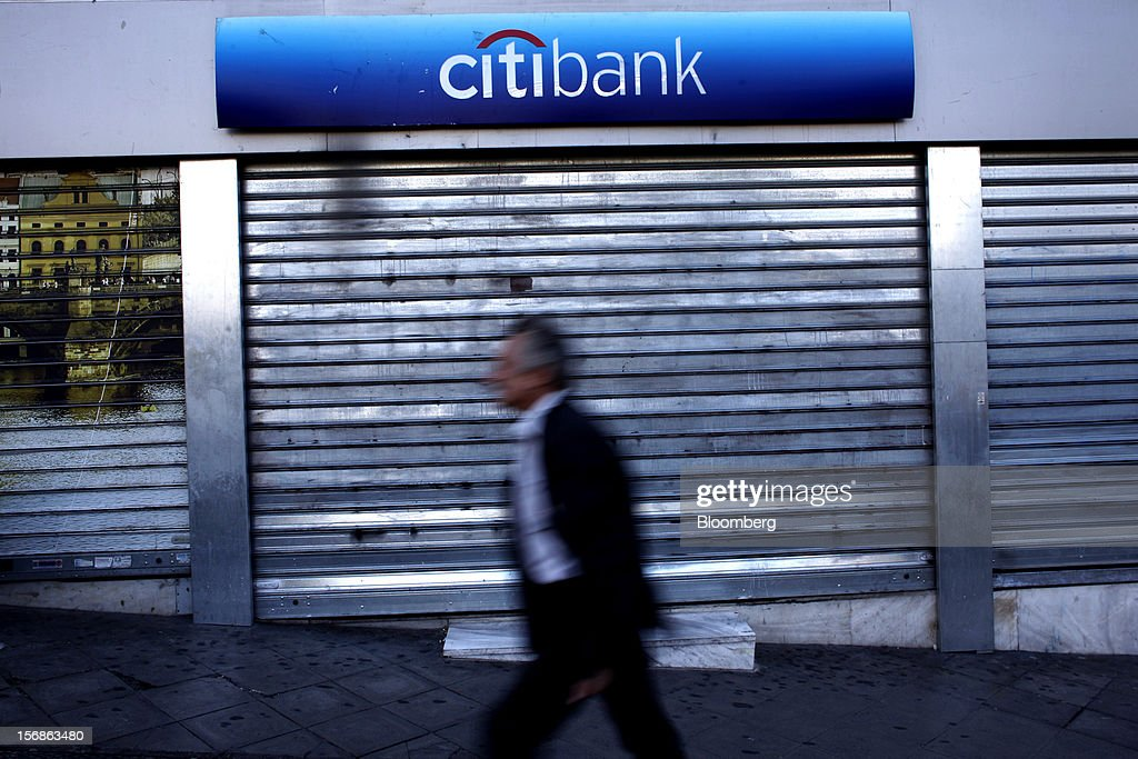 A pedestrian passes a shuttered Citibank branch, operated by Citigroup Inc., in central Athens, Greece, on Thursday, Nov. 22, 2012. Citigroup Inc., the third-biggest U.S. bank by assets, said it will shutter almost half of its branches in Greece as European lawmakers continue a three-year struggle to fix the country's economy. Photographer: Angelos Tzortzinis/Bloomberg via Getty Images