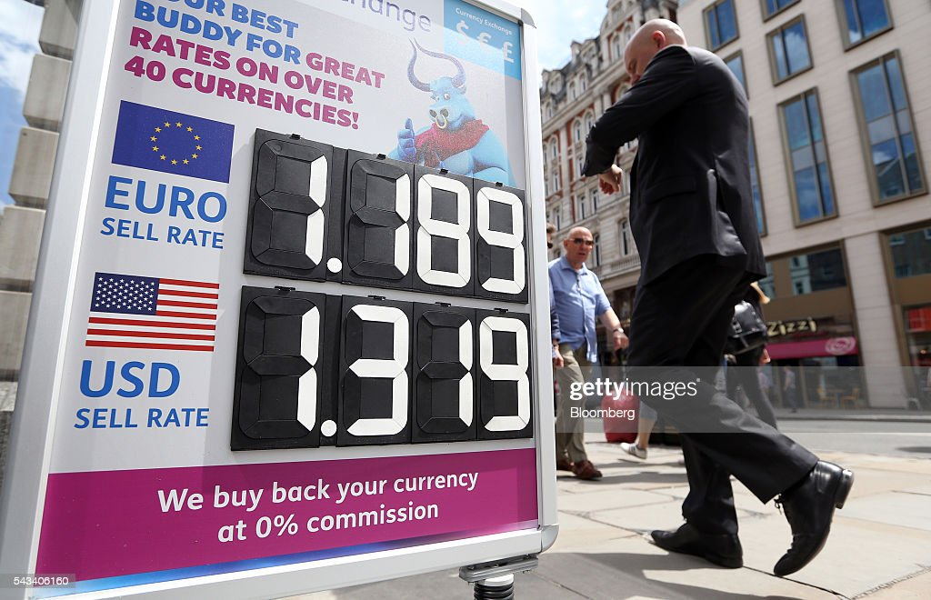 A pedestrian passes a sign advertising euro and U.S. dollar exchange rates outside a foreign currency exchange bureau in London, U.K., on Tuesday, June 28, 2016. The pound rose for the first time since the U.K.s vote to leave the European Union, as a recovery in investor appetite for higher-yielding assets seeped through currency markets. Photographer: Chris Ratcliffe/Bloomberg via Getty Images