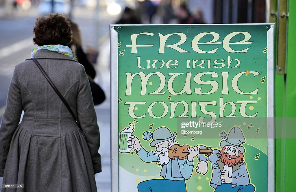 A pedestrian passes a sign advertising Irish music outside a pub in Dublin, Ireland, on Thursday, Dec. 27, 2012. Ireland will take over the EU presidency in January as the euro-area wrestles with putting the European Central Bank in charge of lenders within the currency union and other participating nations. Photographer: Aidan Crawley/Bloomberg via Getty Images