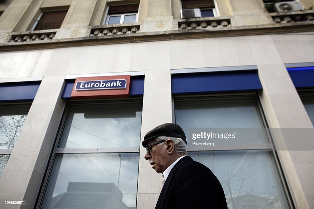 A pedestrian passes a sign outside a Eurobank Ergasias SA bank branch in Athens, Greece, on Tuesday, Jan. 22, 2013. Euro-area finance ministers blessed the next disbursement of emergency aid for Greece, highlighting the goodwill that led to the unblocking of loans last month for Prime Minister Antonis Samaras's government. Photographer: Kostas Tsironis/Bloomberg via Getty Images