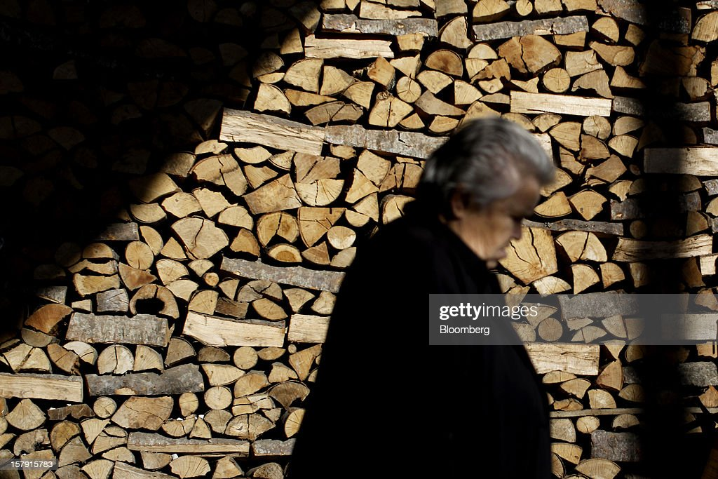 A pedestrian passes a stack of drying firewood at a wood store in Athens, Greece, on Friday, Dec. 7, 2012. Greece, the epicenter of Europe's debt crisis since revealing a bloated spending gap in late 2009, has faced regular demands to get a firmer grip on the budget or risk being forced out of the euro. Photographer: Kostas Tsironis/Bloomberg via Getty Images