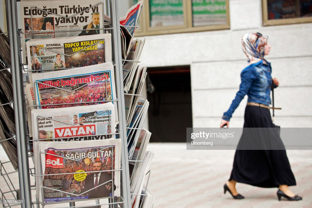 A pedestrian passes a street display of newspapers outside a store in Istanbul, Turkey, on Friday, June 7, 2013. The country's stocks and bonds have slumped this week as demonstrations spread nationwide after police used tear gas and water cannons on May 31 against demonstrators who had gathered in Gezi Park near Taksim to oppose plans to develop it. Photographer: Kerem Uzel/Bloomberg via Getty Images