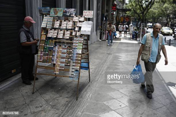 A pedestrian passes a street vendor selling lottery tickets on a sidewalk in Athens Greece on Thursday June 29 2017 The change in sentiment toward...