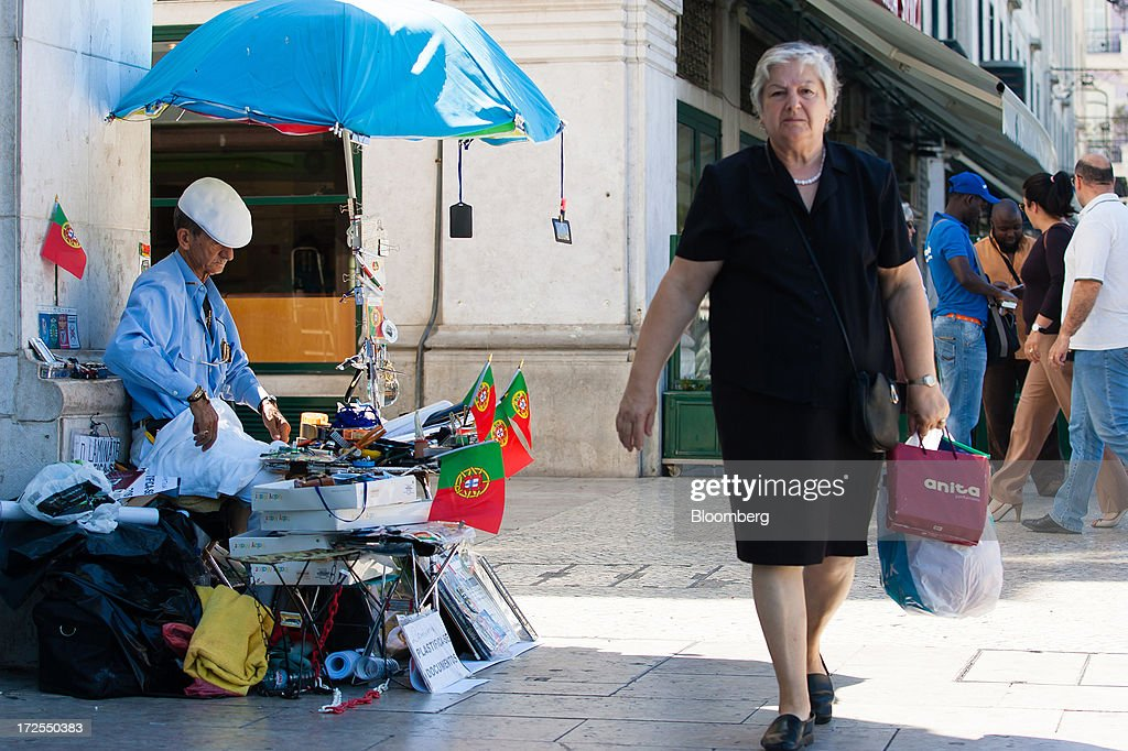 A pedestrian passes a street vendor with a display of Portuguese national flags on Rossio plaza in Lisbon, Portugal, on Wednesday, July 3, 2013. Portuguese borrowing costs topped 8 percent for the first time this year after two ministers quit, signaling the government will struggle to implement further budget cuts as its bailout program enters its final 12 months. Photographer: Mario Proenca/Bloomberg via Getty Images