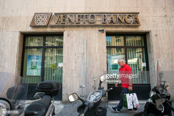 A pedestrian passes a Veneto Banca SpA bank branch in Rome Italy on Monday June 26 2017 Italy orchestrated its biggest bank rescue on record...
