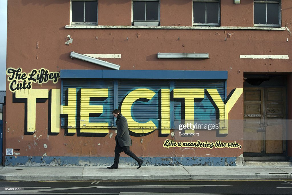 A pedestrian passes a wall covered in graffiti which reads 'The Liffey Cuts The City Like a Meandering Blue Vein' at North Wall Quay in Dublin, Ireland, on Friday, March 15, 2013. Ireland's renewed competiveness makes it a beacon for the U.S. companies such as EBay, Google Inc. and Facebook Inc., which have expanded their operations in the country over the past two years. Photographer: Simon Dawson/Bloomberg via Getty Images