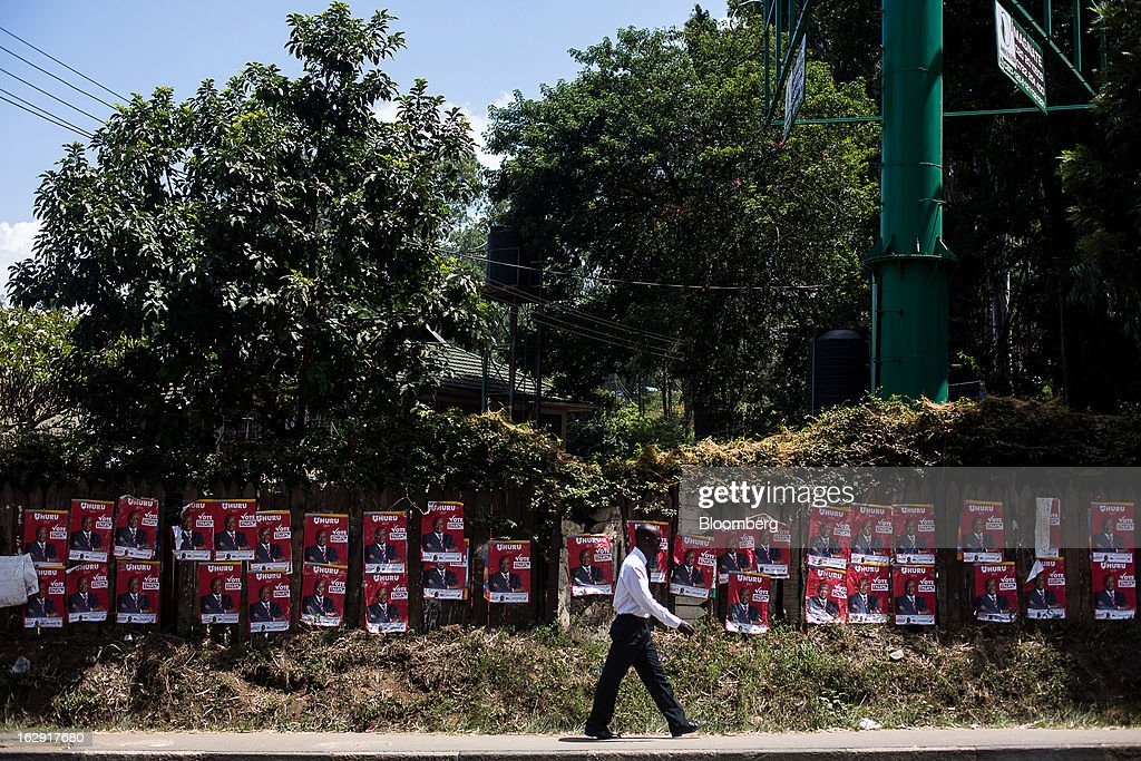 A pedestrian passes a wall of election posters for Uhuru Kenyatta, Kenya's deputy premier, on a street ahead of the presidential election in Nairobi, Kenya, on Friday, March 1, 2013. Next week's presidential vote will be the first since disputed elections in 2007 triggered ethnic fighting in which more than 1,100 people died and another 350,000 fled their homes. Photographer: Trevor Snapp/Bloomberg via Getty Images