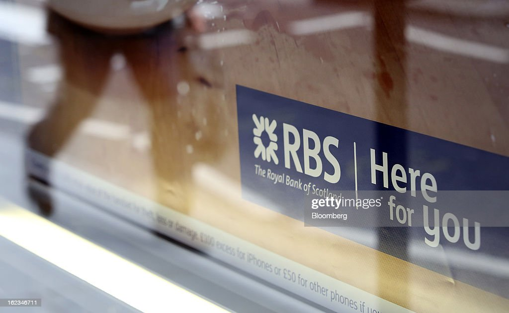 A pedestrian passes a window advertisement outside a branch of Royal Bank of Scotland Group Plc (RBS), in London, U.K., on Friday, Feb. 22, 2013. RBS, Britain's biggest publicly owned lender, was fined $612 million by regulators in the U.K. and the U.S. for rigging the London interbank offered rate and similar benchmarks. Photographer: Chris Ratcliffe/Bloomberg via Getty Images