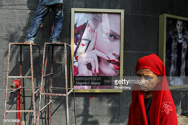 A pedestrian passes a worker hanging advertisements outside the new Marks Spencer Reliance India Pvt store in the Bandra area of Mumbai India on...