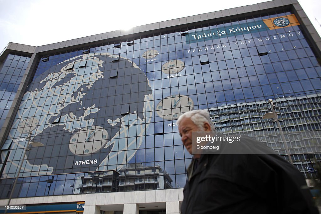 A pedestrian passes a world map design with time zones for Nicosia, Athens, Sydney and New York on the facade of the headquarters of the Bank of Cyprus Plc in Athens, Greece, on Tuesday, March 19, 2013. Cyprus's passage of an unprecedented levy on bank deposits was in doubt as euro-area finance ministers responded to criticism of the measure by loosening their stance on how the money is raised. Photographer: Kostas Tsironis/Bloomberg via Getty Images