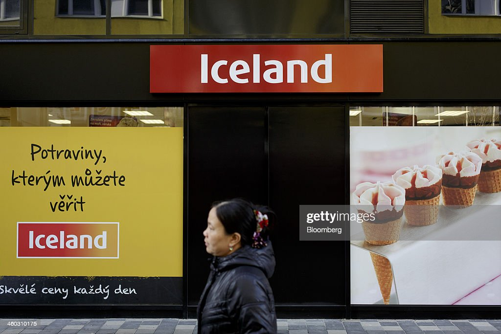A pedestrian passes advertisements and logos outside an Iceland Foods Ltd. frozen food store in Prague, Czech Republic, on Friday, Jan. 3. 2014. The Czech Republic's 2013 budget deficit of 80.9 billion koruna ($4.01 billion) beat the 100 billion-koruna target after the government cut spending, the Finance Ministry said. Photographer: Martin Divisek/Bloomberg via Getty Images