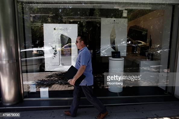 A pedestrian passes advertisements for Apple Inc iPhone 6 smart phones and MacBook laptops in the window display of an electric goods store in Athens...