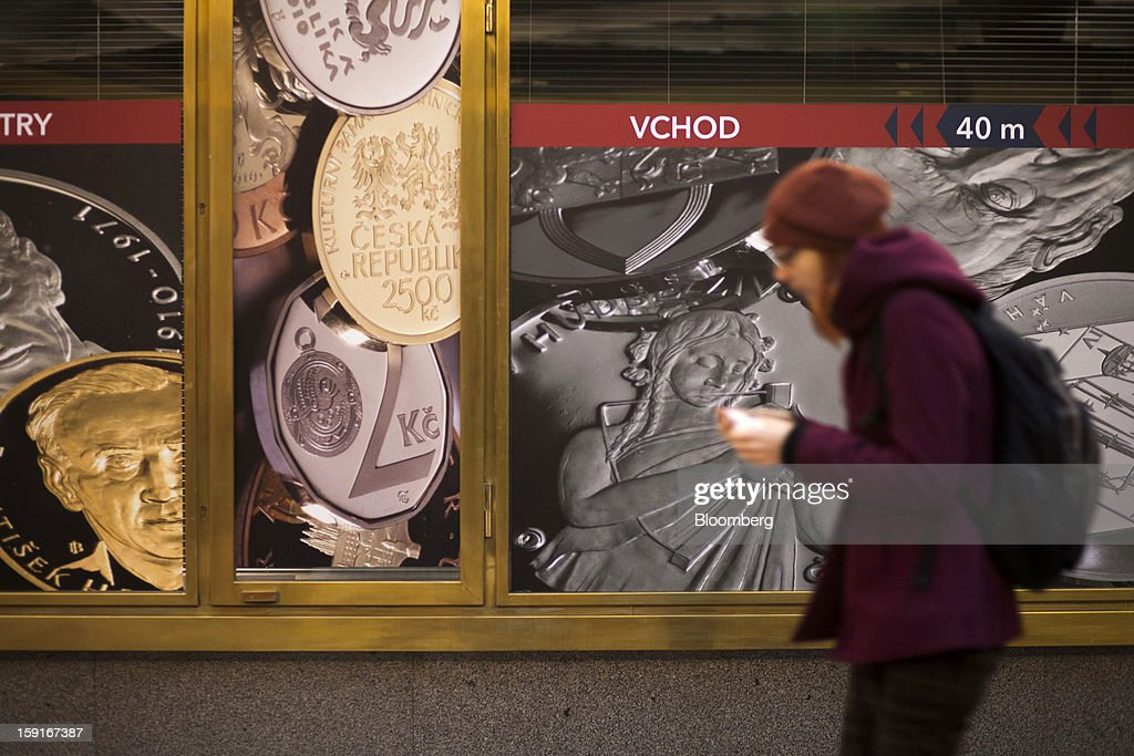 A pedestrian passes advertisements for koruna currency coins in Prague, Czech Republic, on Tuesday, Jan. 8, 2013. The Czech economy is showing weak domestic demand as households and businesses cut spending due to government austerity programs and the euro area's debt crisis. Photographer: Bartek Sadowski/Bloomberg via Getty Images