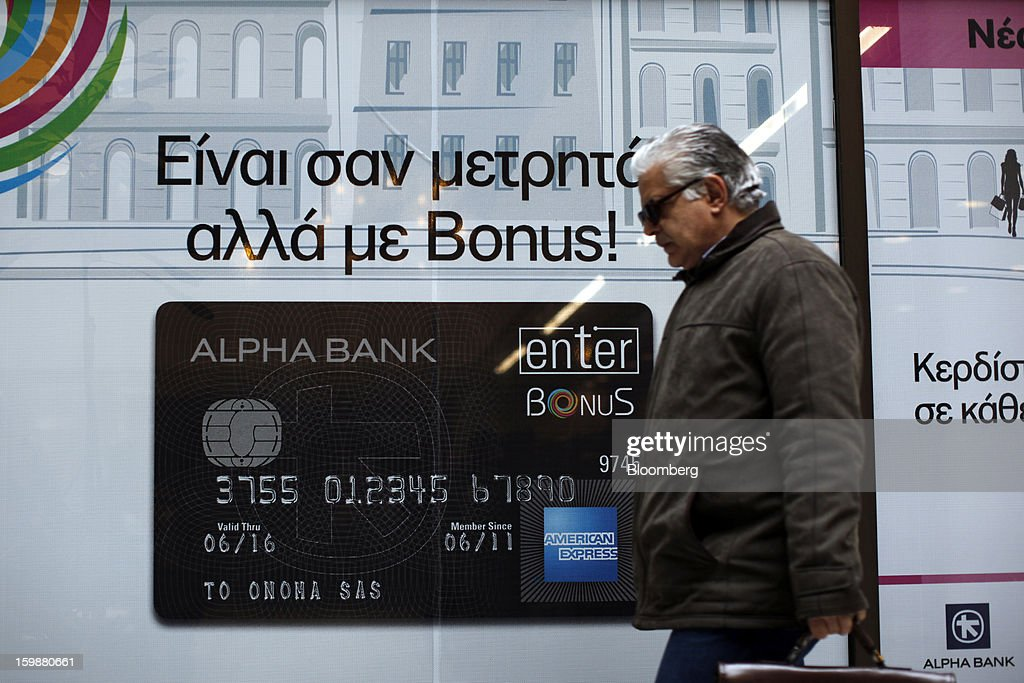 A pedestrian passes an advertisement for an American Express credit card in the window of an Alpha Bank AE branch in Athens, Greece, on Tuesday, Jan. 22, 2013. Euro-area finance ministers blessed the next disbursement of emergency aid for Greece, highlighting the goodwill that led to the unblocking of loans last month for Prime Minister Antonis Samaras's government. Photographer: Kostas Tsironis/Bloomberg via Getty Images