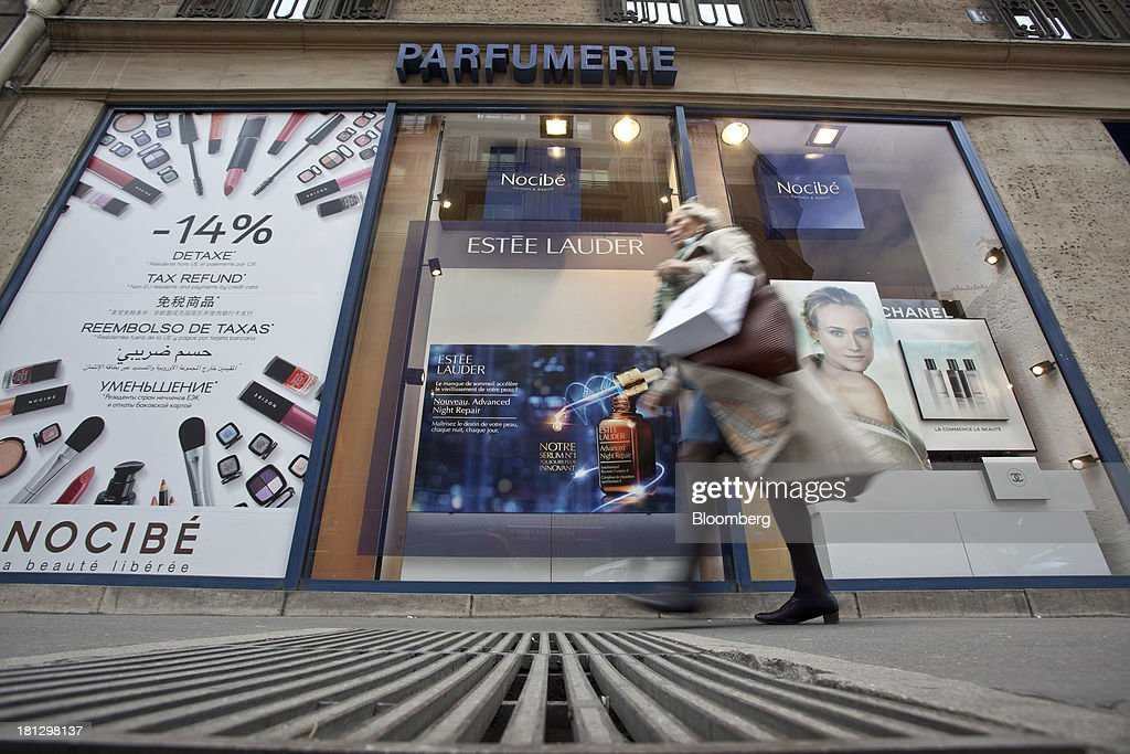 A pedestrian passes an advertisement for Estee Lauder Cos. in the window display of a Nocibe SA beauty store in Paris, France, on Thursday, Sept. 19, 2013. Bank of France General Council member Bernard Maris said France will end up restructuring its debt as tax 'optimization' by large companies including Google Inc. will leave too big a burden on the middle class. Photographer: Balint Porneczi/Bloomberg via Getty Images