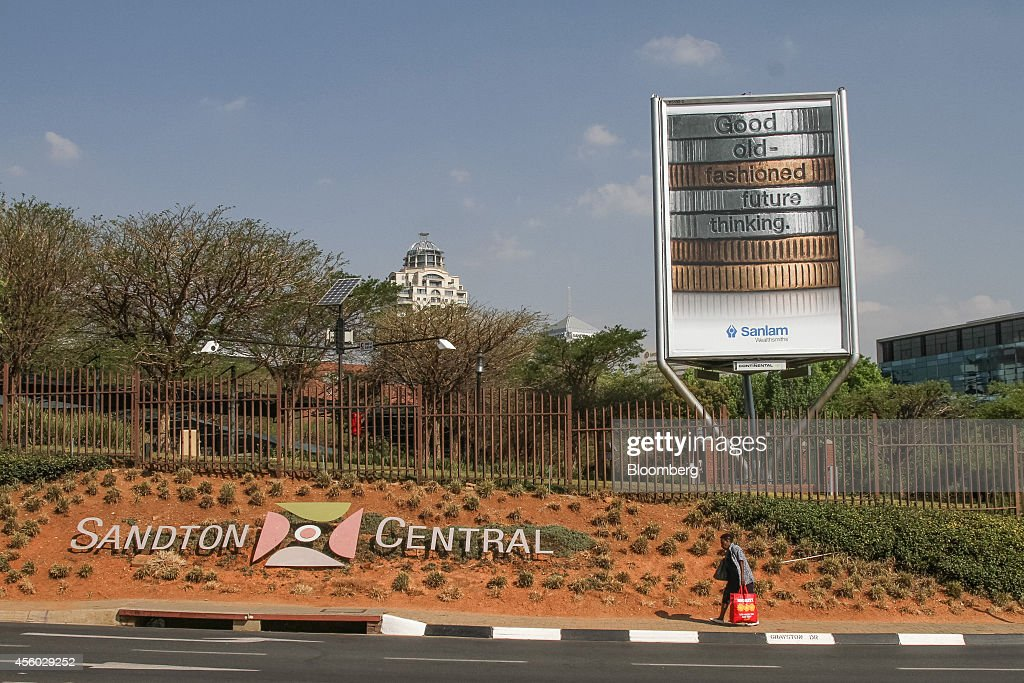 A pedestrian passes an advertisement for Sanlam Ltd financial services group on a roadside in central Sandton South Africa on Tuesday Sept 23 2014...