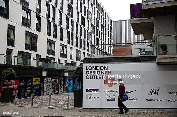 A pedestrian passes an advertisement for stores located at the London Designer Outlet part of the Wembley Park complex a joint retail and residential...