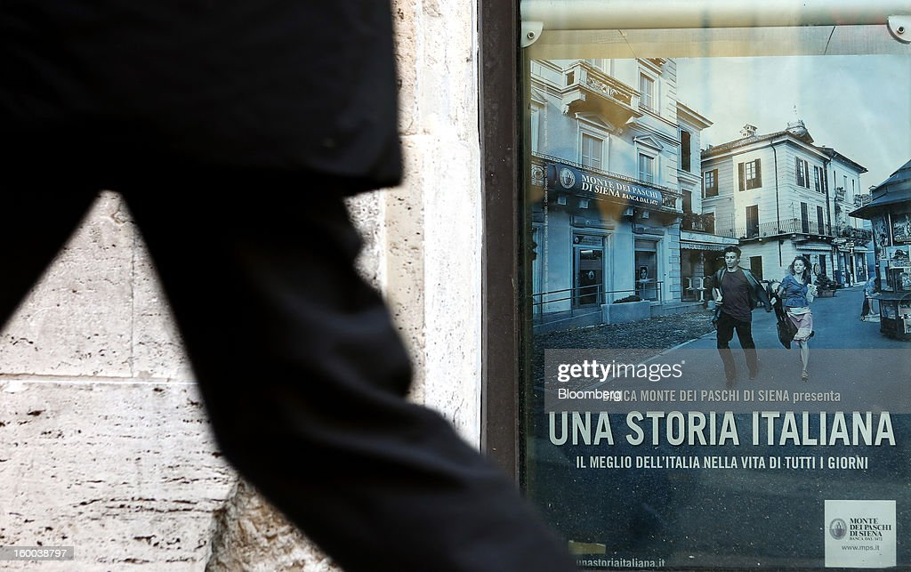 A pedestrian passes an advertisement in the window of a Banca Monte dei Paschi di Siena SpA bank branch in Rome, Italy, on Friday, Jan. 25, 2013. Italian Prime Minister Mario Monti said the Bank of Italy will take another look at Banca Monte dei Paschi di Siena SpA's books after the company disclosed this week it may face more than 700 million euros of losses related to structured finance transactions hidden from regulators. Photographer: Alessia Pierdomenico/Bloomberg via Getty Images