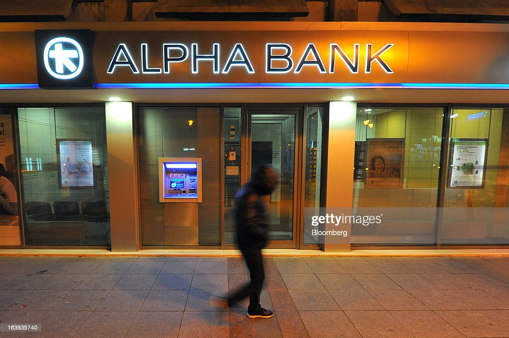 A pedestrian passes an Alpha Bank AE branch illuminated at night in central Skopje, Macedonia, on Saturday, March 16, 2013. Macedonia's economy contracted by a real 0.3% on the year in 2012, compared to a growth of 2.8% a year earlier, an estimate released by the country's statistics office showed. Photographer: Oliver Bunic/Bloomberg via Getty Images