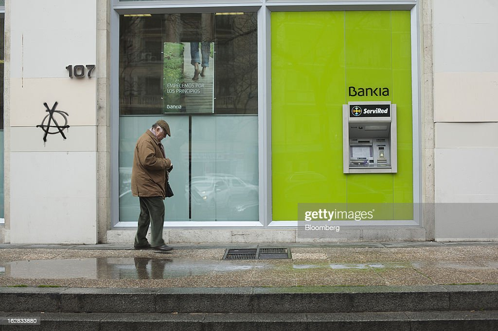 A pedestrian passes an automated teller machines (ATM) outside a Bankia SA branch in Madrid, Spain, on Thursday, Feb. 28, 2013. BFA-Bankia Chairman Jose Ignacio Goirigolzarri said a balance sheet clean-up that inflicted a 21.2 billion-euro ($27.6 billion) after-tax loss last year will set the Spanish banking group on course to repay state aid. Photographer: Angel Navarrete/Bloomberg via Getty Images