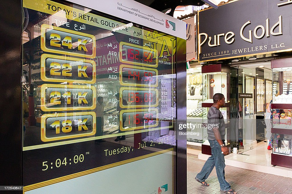 A pedestrian passes an electronic display showing the latest gold trading prices in the Dubai Gold Souk in the Deira district of Dubai, United Arab Emirates, on Tuesday, July 2, 2013. Gold swung between gains and losses in London as investors weighed prospects for increased physical demand against a slowing stimulus in the U.S. Photographer: Duncan Chard/Bloomberg via Getty Images