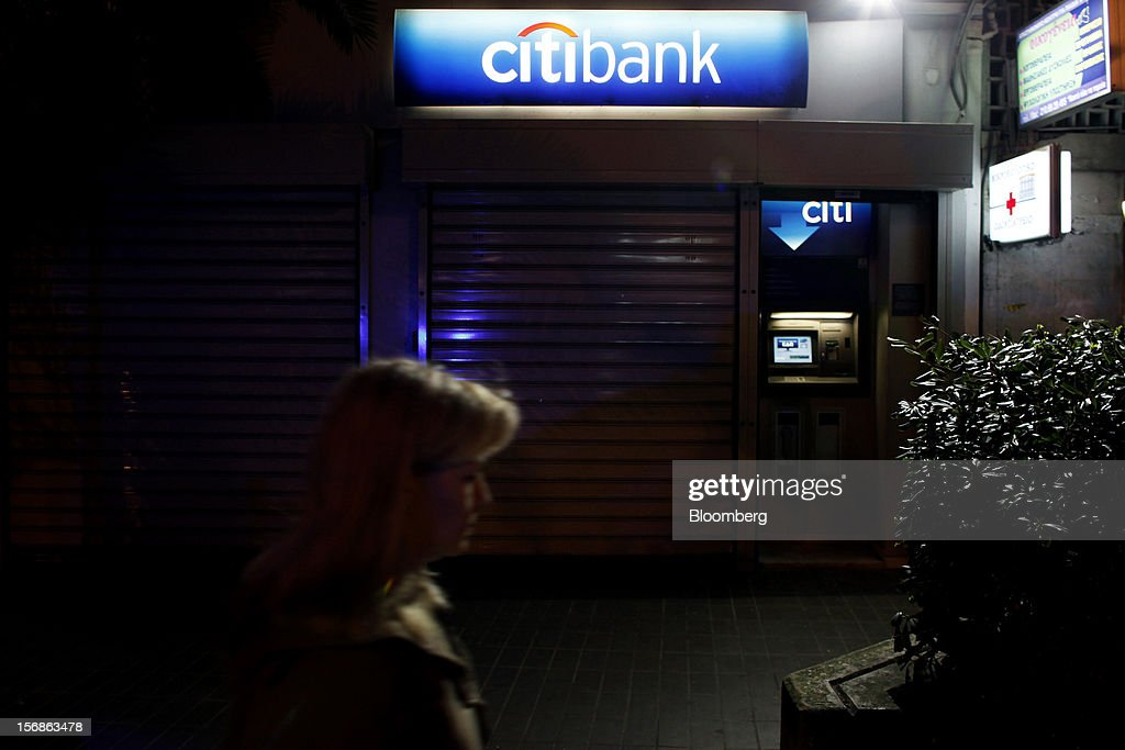 A pedestrian passes an illuminated automated teller machine (ATM) and logo outside a shuttered Citibank branch, operated by Citigroup Inc., in central Athens, Greece, on Thursday, Nov. 22, 2012. Citigroup Inc., the third-biggest U.S. bank by assets, said it will shutter almost half of its branches in Greece as European lawmakers continue a three-year struggle to fix the country's economy. Photographer: Kostas Tsironis/Bloomberg via Getty Images