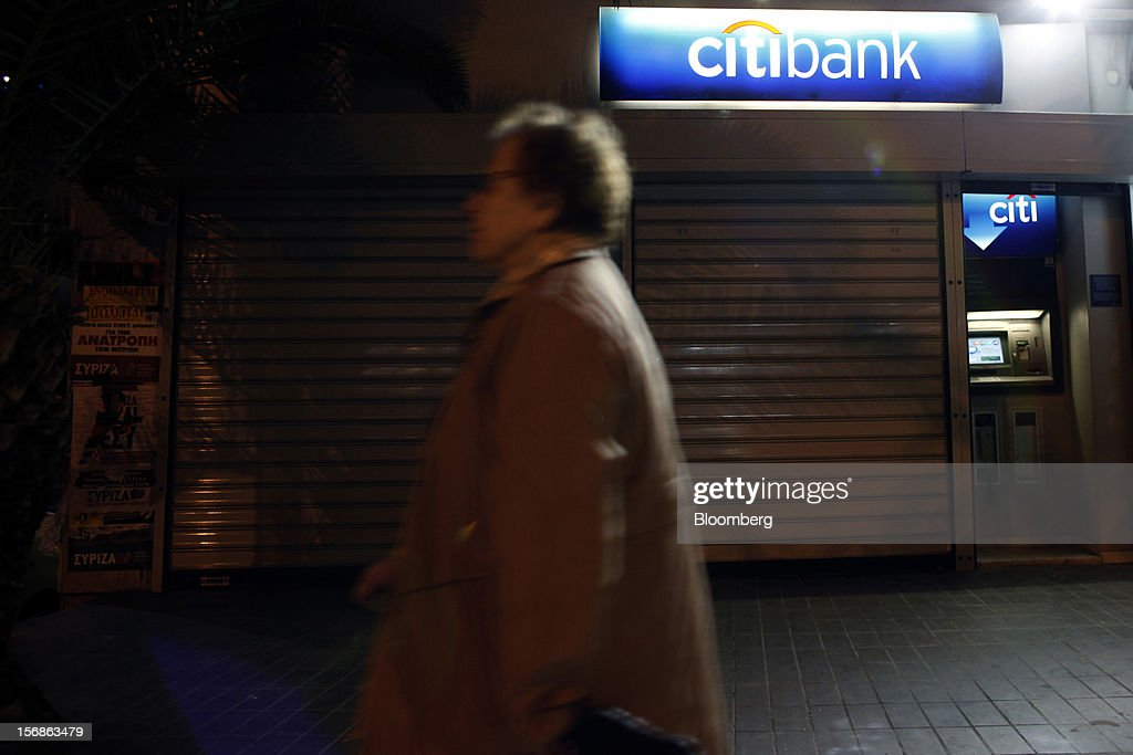 A pedestrian passes an illuminated automated teller machine (ATM) and logo outside a shuttered Citibank branch, operated by Citigroup Inc., in central Athens, Greece, on Thursday, Nov. 22, 2012. Citigroup Inc., the third-biggest U.S. bank by assets, said it will shutter almost half of its branches in Greece as European lawmakers continue a three-year struggle to fix the country's economy. Photographer: Angelos Tzortzinis/Bloomberg via Getty Images