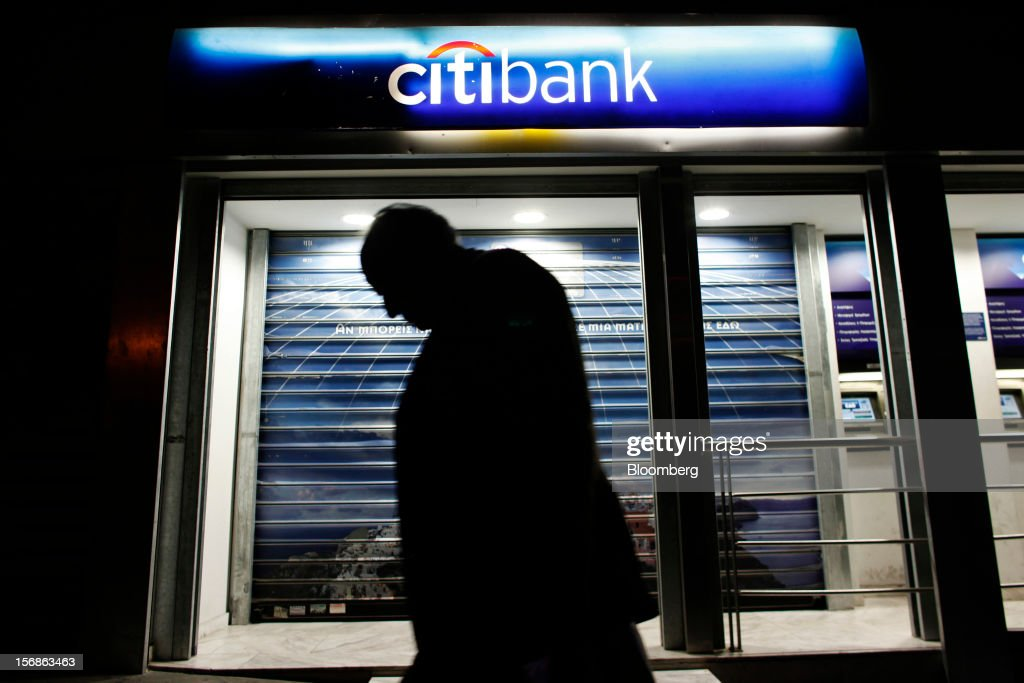 A pedestrian passes an illuminated Citibank branch, operated by Citigroup Inc., in central Athens, Greece, on Thursday, Nov. 22, 2012. Citigroup Inc., the third-biggest U.S. bank by assets, said it will shutter almost half of its branches in Greece as European lawmakers continue a three-year struggle to fix the country's economy. Photographer: Kostas Tsironis/Bloomberg via Getty Images Photographer: Angelos Tzortzinis/Bloomberg via Getty Images