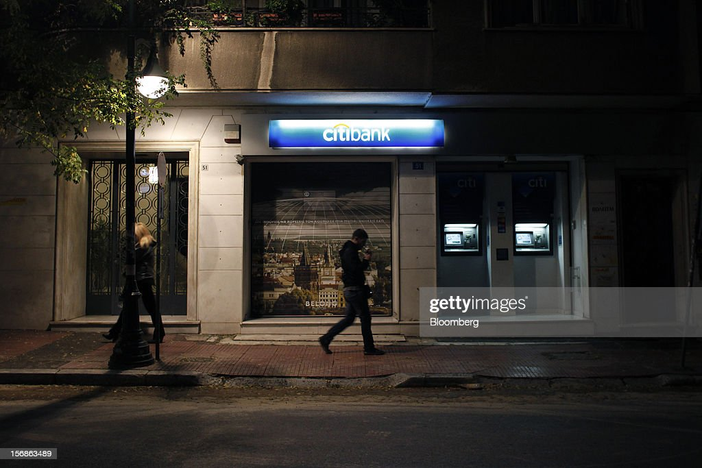 A pedestrian passes an illuminated Citibank branch, operated by Citigroup Inc., in central Athens, Greece, on Thursday, Nov. 22, 2012. Citigroup Inc., the third-biggest U.S. bank by assets, said it will shutter almost half of its branches in Greece as European lawmakers continue a three-year struggle to fix the country's economy. Photographer: Angelos Tzortzinis/Bloomberg via Getty Images