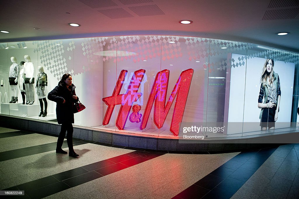 A pedestrian passes an illuminated logo in the window of a Hennes & Mauritz AB (H&M) store in Stockholm, Sweden, on Tuesday, Jan. 29, 2013. Hennes & Mauritz AB, Europe's second-largest clothing retailer, reported sales growth that beat analysts' estimates for a second consecutive month as the chain offered markdowns in advance of the Christmas holiday. Photographer: Casper Hedberg/Bloomberg via Getty Images