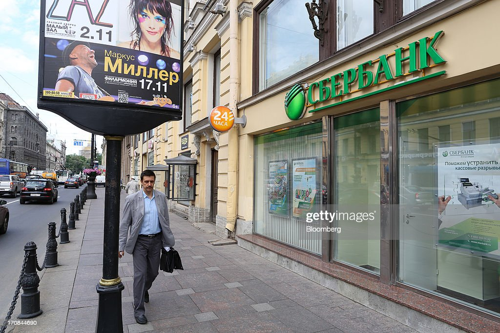 A pedestrian passes an OAO Sberbank bank branch ahead of the St. Petersburg International Economic Forum 2013 (SPIEF) in St. Petersburg, Russia, on Wednesday, June 19, 2013. The Russian Deputy Prime Minister Igor Shuvalov told the conference that the country's World Trade Organization accession negotiations could be further delayed unless several remaining disputed matters are solved. Photographer: Andrey Rudakov/Bloomberg via Getty Images
