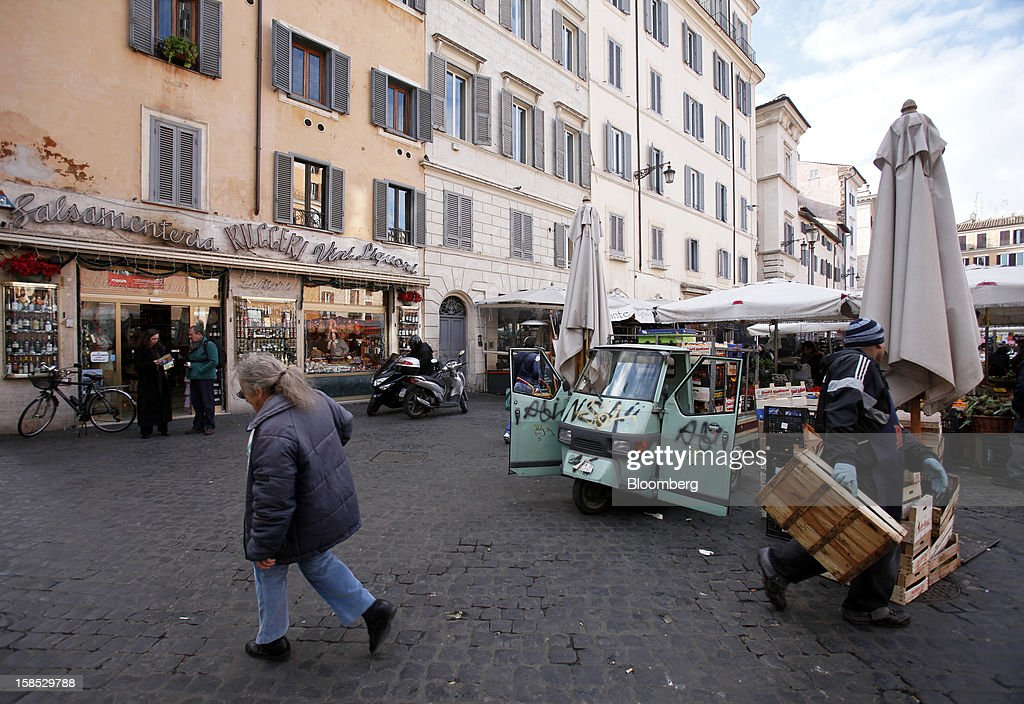 A pedestrian passes an outdoor street market in Rome, Italy, on Tuesday, Dec. 18, 2012. Italian Prime Minister Mario Monti, who is under pressure from euro-area and business leaders to enter the Italian election campaign, plans to quit once parliament passes his budget this week. Photographer: Alessia Pierdomenico/Bloomberg via Getty Images