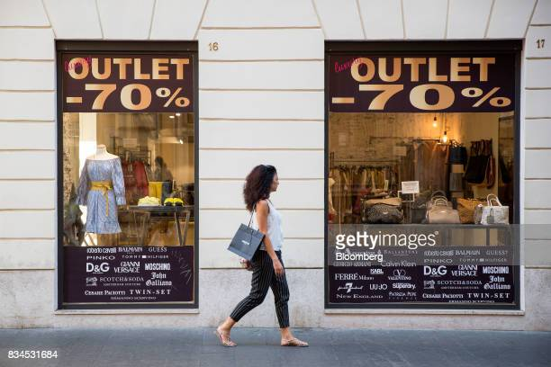 A pedestrian passes an outlet luxury clothing store in Rome Italy on Thursday Aug 17 2017 Italy's economic recovery extended for a tenth straight...
