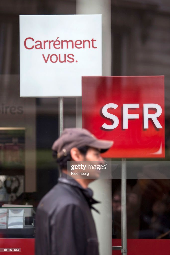 A pedestrian passes an SFR store, a mobile-phone unit of Vivendi SA, in Paris, France, on Thursday, Sept. 19, 2013. Bank of France General Council member Bernard Maris said France will end up restructuring its debt as tax 'optimization' by large companies including Google Inc. will leave too big a burden on the middle class. Photographer: Balint Porneczi/Bloomberg via Getty Images