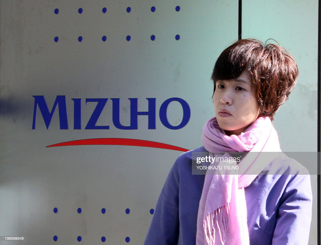 A pedestrian passes before a branch of Japan's mega bank Mizuho bank in Tokyo on November 14, 2012. Mizuho Financial Group said its net profit in the first half slipped 27.6 percent to 2.3 billion USD, but its sales and operating profit rose on its healthy market operation. Net profit in six months to September slumped to 184.3 billion yen, mainly a relative impact from last year when the bank added a wholly owned subsidiary and boosted profit figures. AFP PHOTO / Yoshikazu TSUNO