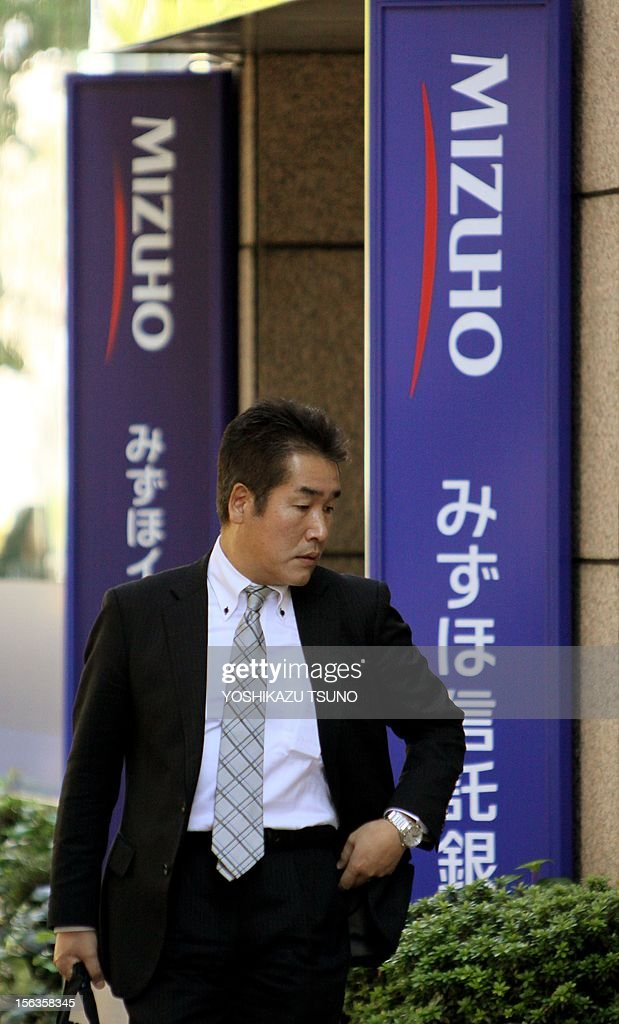 A pedestrian passes before a branch of Japan's Mizuho Trust bank in Tokyo on November 14, 2012. Mizuho Financial Group said its net profit in the first half slipped 27.6 percent to 2.3 billion USD, but its sales and operating profit rose on its healthy market operation. Net profit in six months to September slumped to 184.3 billion yen, mainly a relative impact from last year when the bank added a wholly owned subsidiary and boosted profit figures. AFP PHOTO / Yoshikazu TSUNO